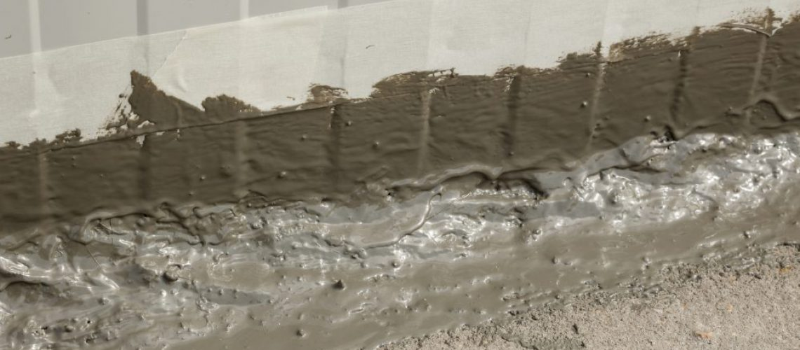 Close up of the first layer of an waterproofing ms polymer sealant freshly applied on an outside wall-floor connection