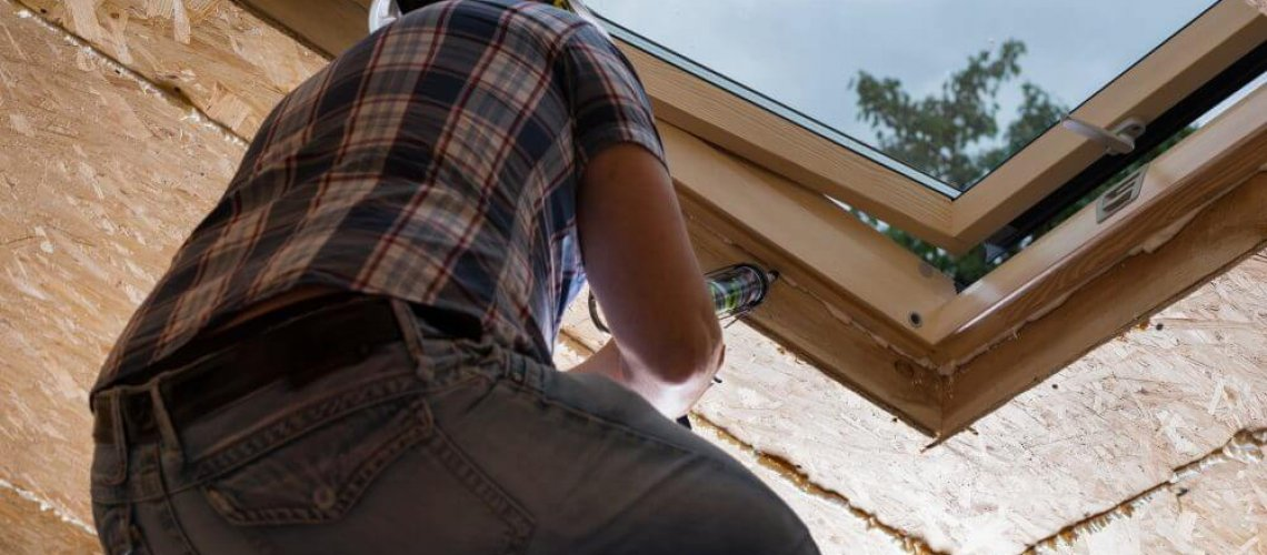 Low Angle View of Male Construction Worker Builder Applying Fresh Caulking to Sky Light in Ceiling of Unfinished Home